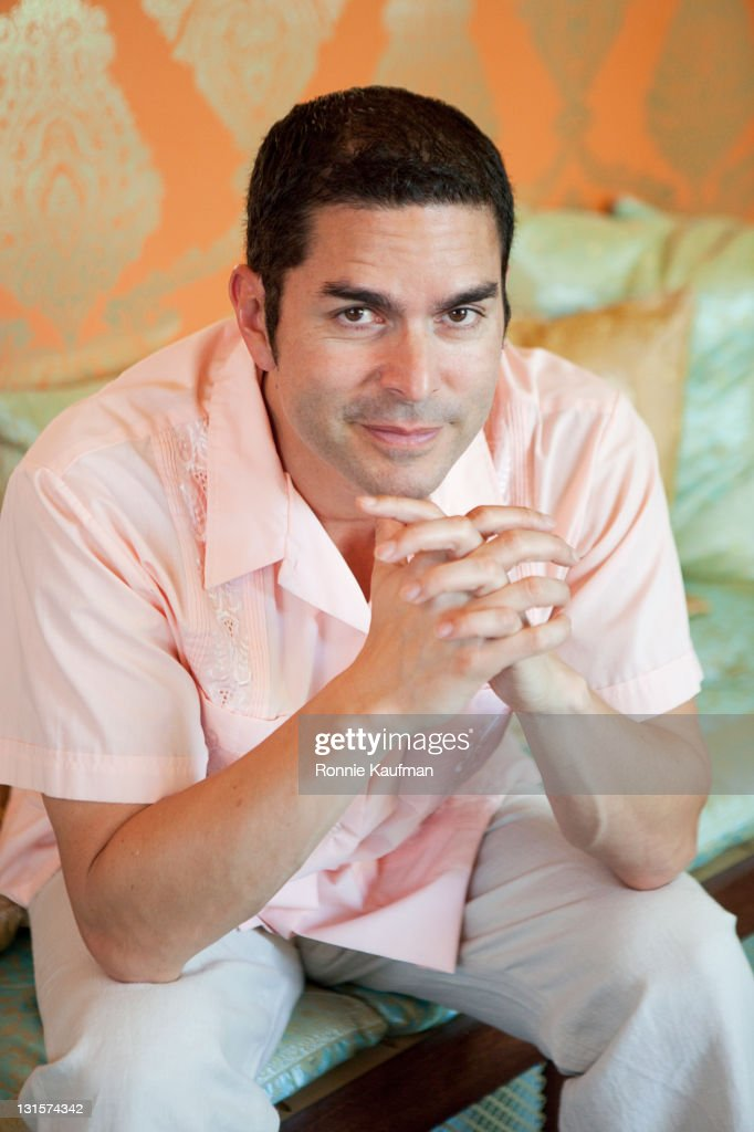Hispanic man sitting with hands clasped : Stock Photo