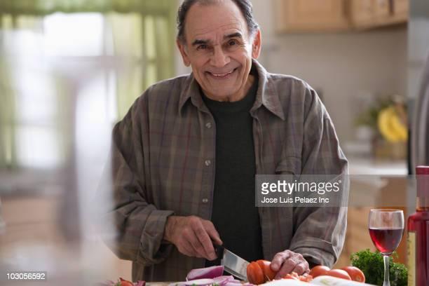 Hispanic man slicing tomatoes