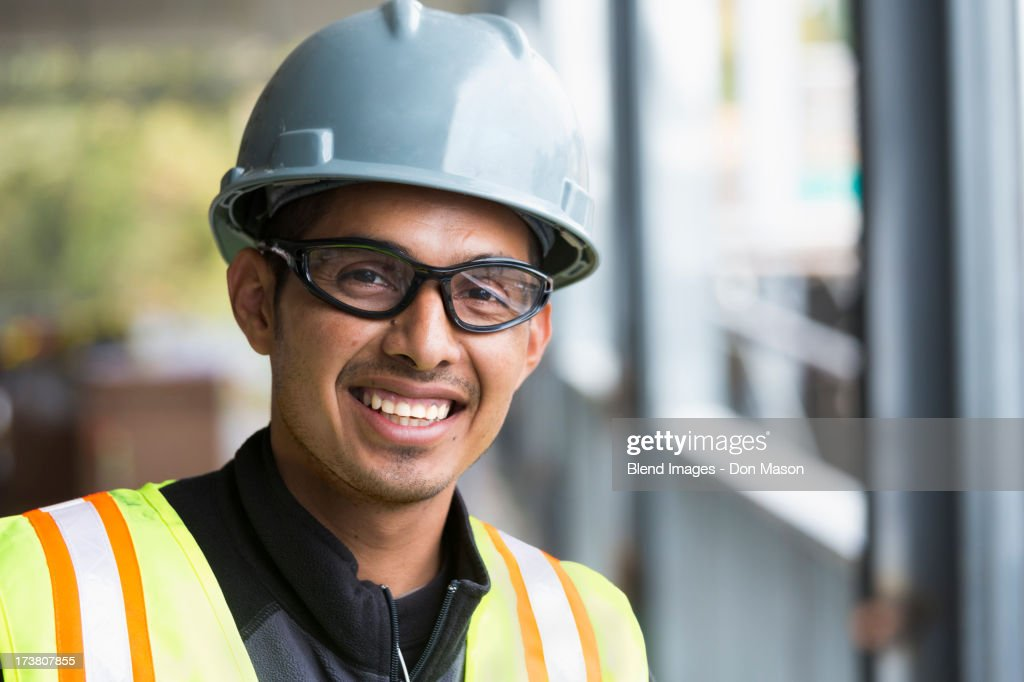 Hispanic man smiling at construction site