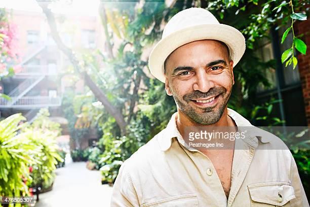 Hispanic man smiling in courtyard