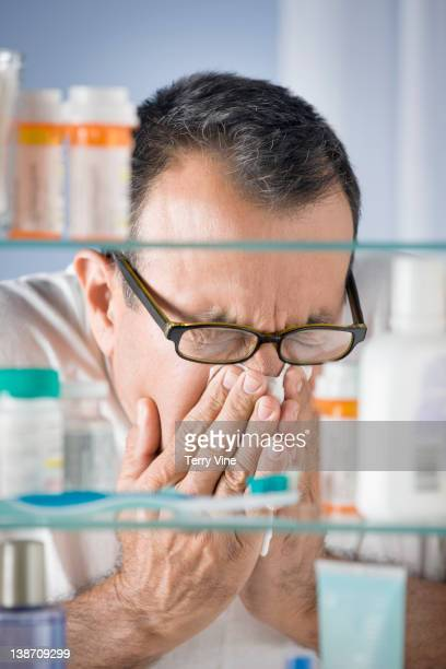 Hispanic man sneezing in bathroom