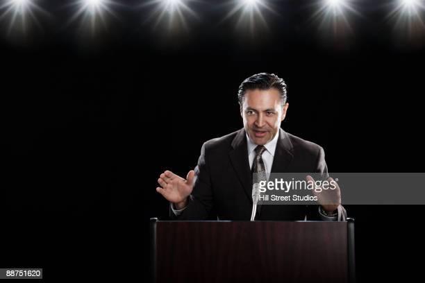 Hispanic man speaking at podium