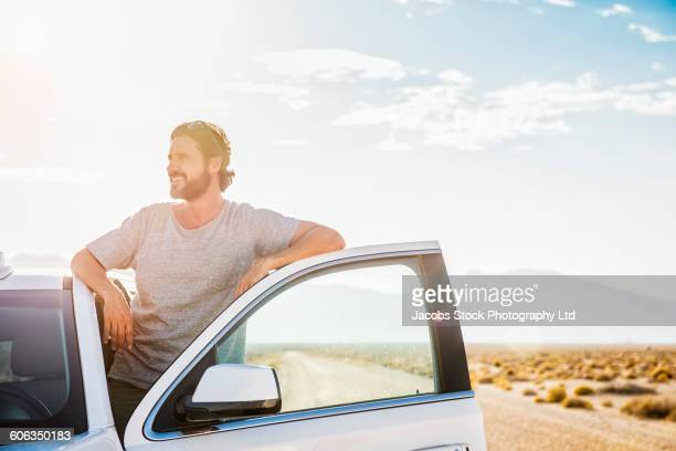 Hispanic man standing in car on remote road