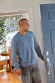 Hispanic man standing in front of a door and smiling