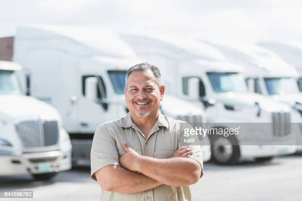 Hispanic man standing in front of semi-trucks