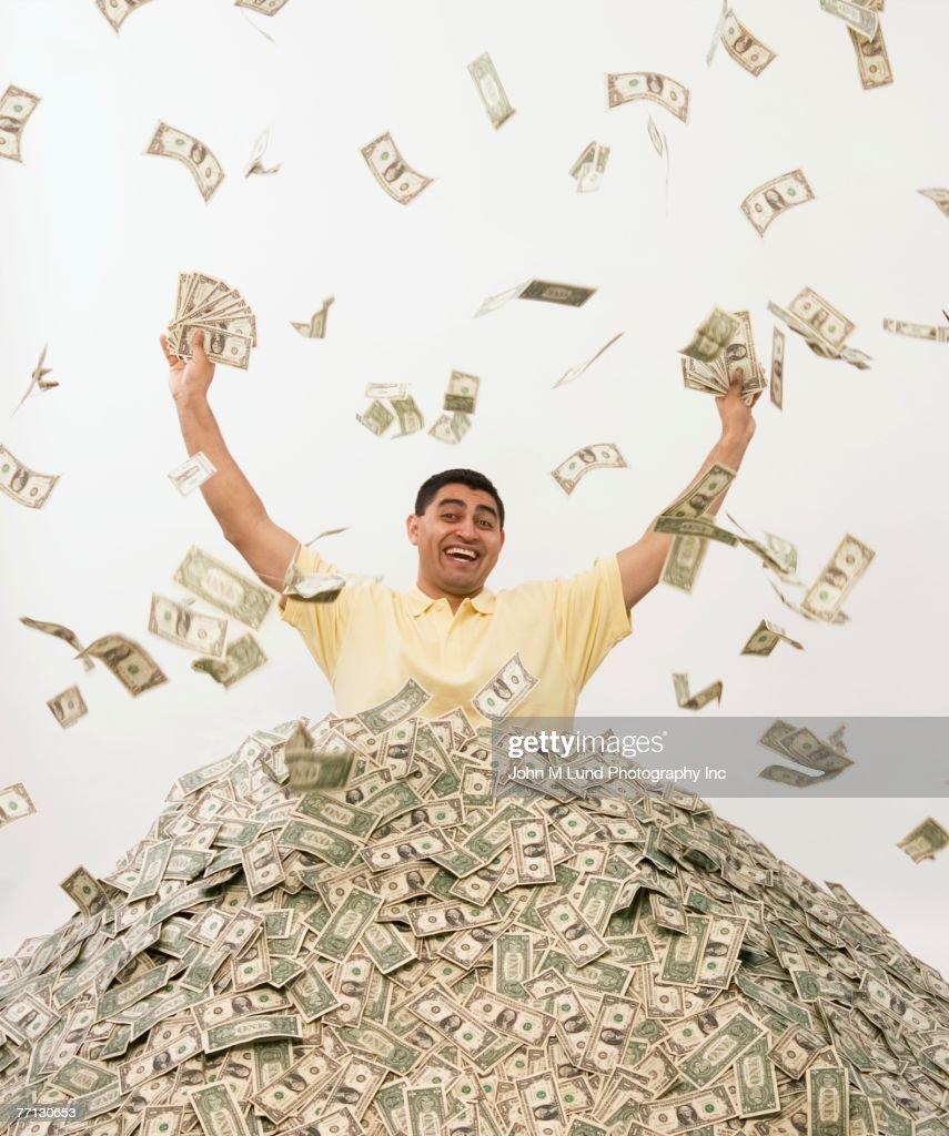 Hispanic man standing in pile of money : Stock Photo