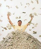 Hispanic man standing in pile of money
