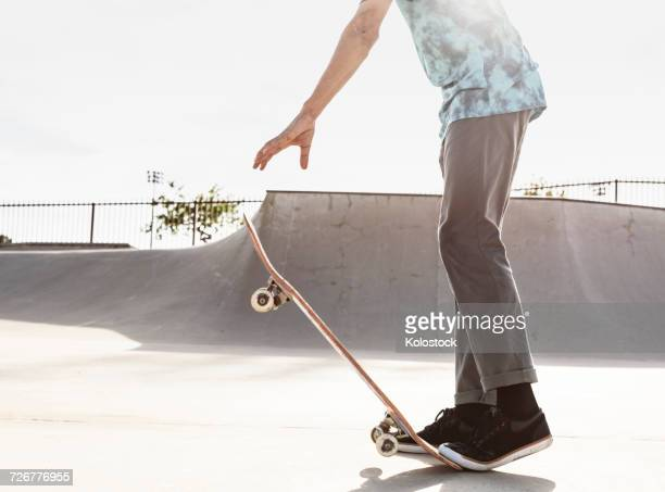 Hispanic man stepping on tail of skateboard