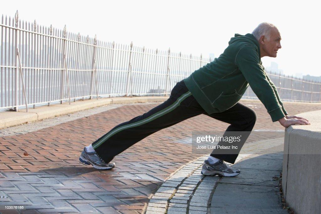 Hispanic man stretching in urban setting