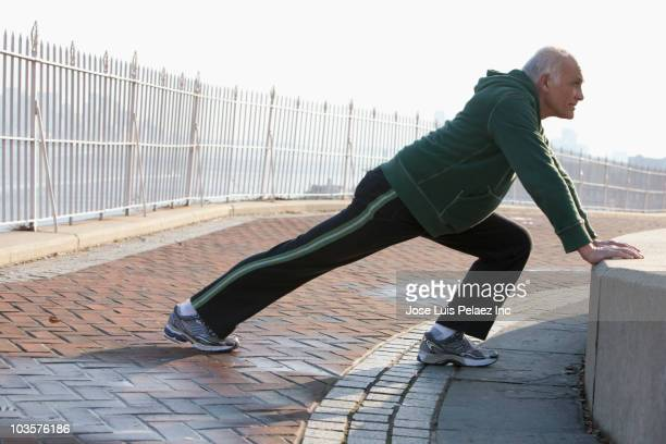 Hispanic man stretching in urban setting