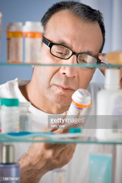 Hispanic man taking medicine from bathroom cabinet