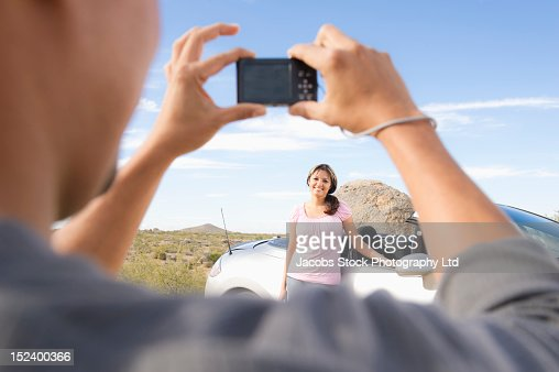 Hispanic man taking photograph of wife next to sports car : Stock Photo