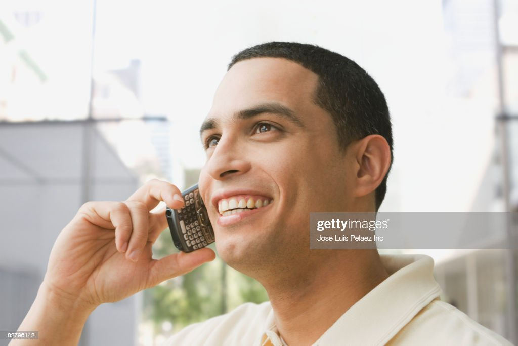 Hispanic man talking on cell phone outdoors : Stock Photo