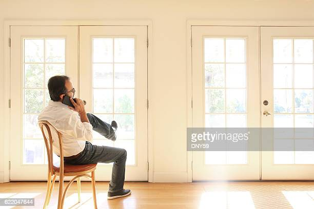 Hispanic Man Talking On Cell Phone Sits In Chair