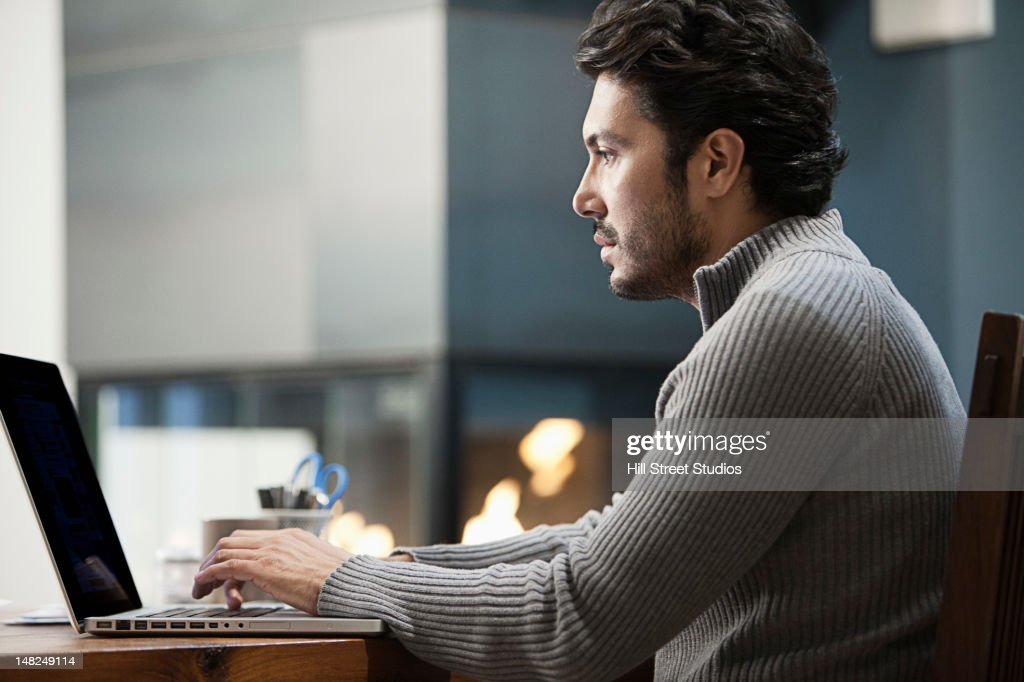 Hispanic man typing on laptop : Stock Photo