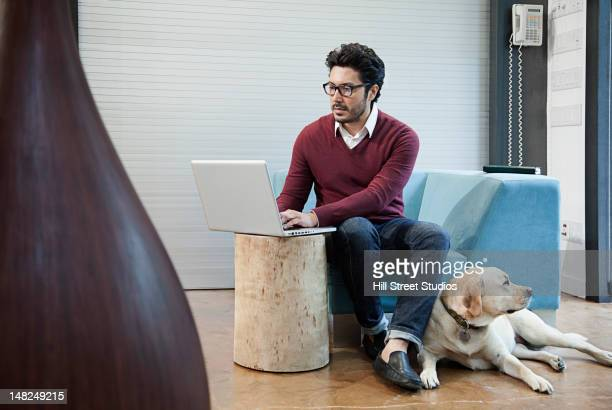 Hispanic man typing on laptop with dog by his side