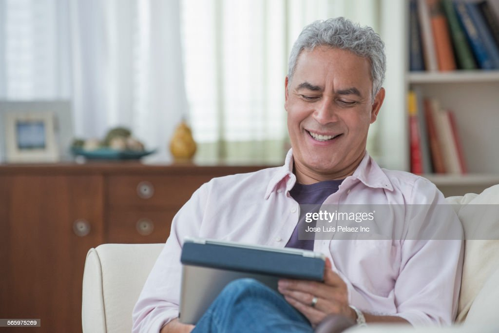 Hispanic man using digital tablet on sofa