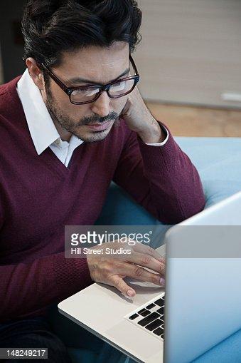 Hispanic man using laptop : Stock Photo