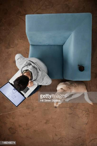 Hispanic man using laptop with dog at his feet