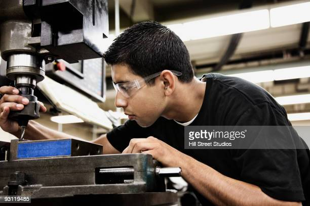 Hispanic man using machine in machine shop