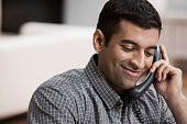 Hispanic man using telephone in home office