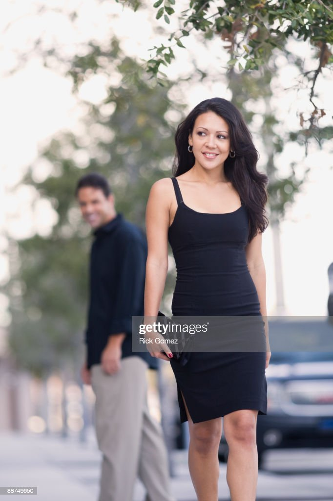 Hispanic man watch sexy woman walk down the street : Stock Photo