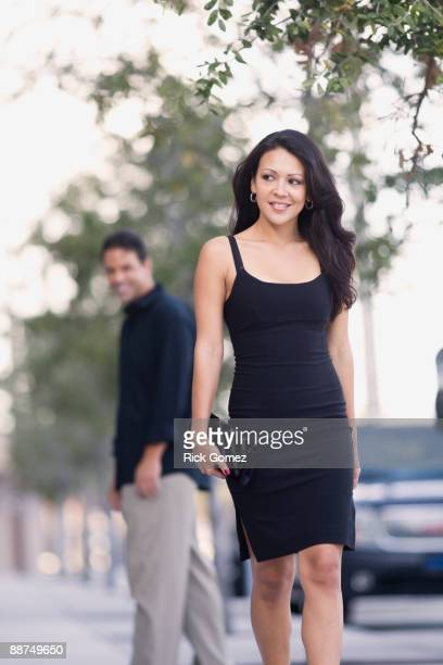 Hispanic man watch sexy woman walk down the street