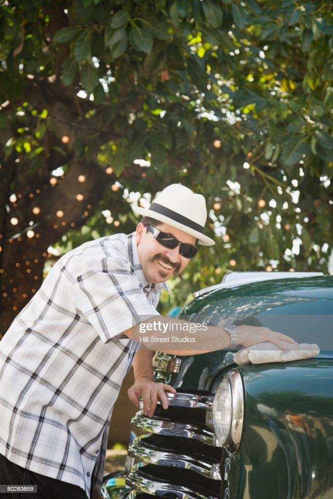 Hispanic man waxing truck : Stock Photo