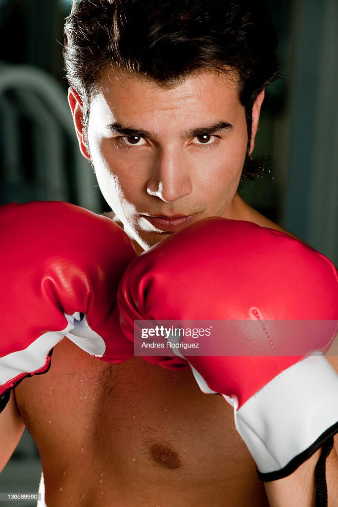 Hispanic man wearing boxing gloves : Stock Photo