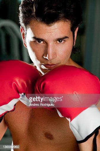 Hispanic man wearing boxing gloves : Stockfoto