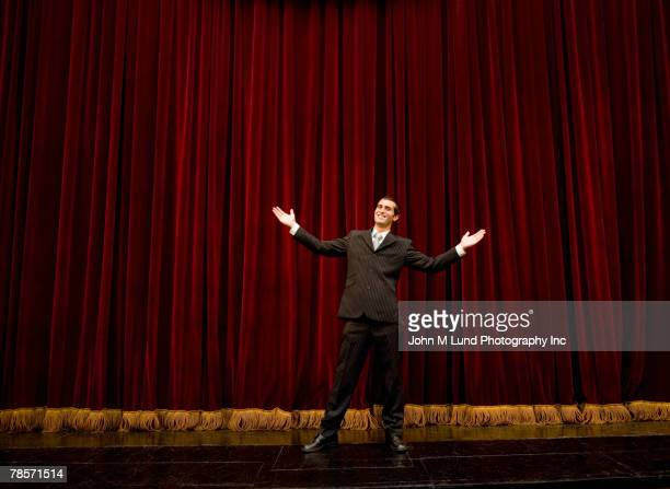 Hispanic man with arms outstretched on stage