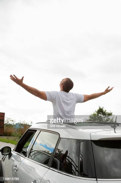 Hispanic man with arms outstretched standing in sun roof