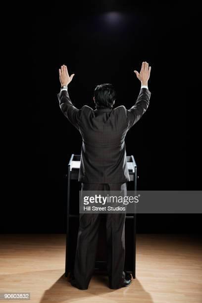 Hispanic man with arms raised at podium
