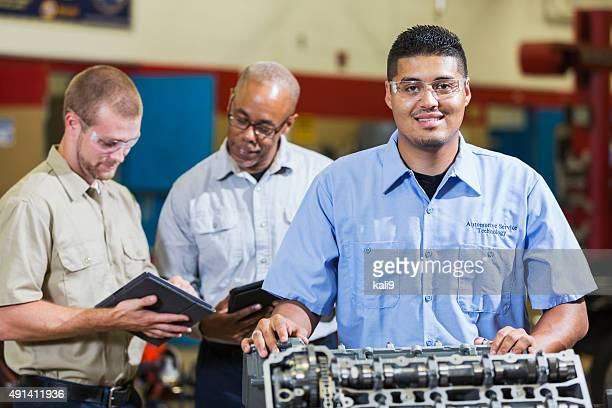 Homme hispanique avec moteur, collègues sur tablettes numériques