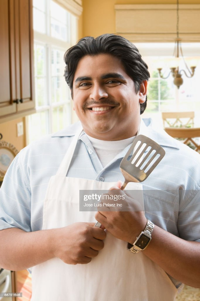 Hispanic man with spatula preparing to make dinner : Stock Photo