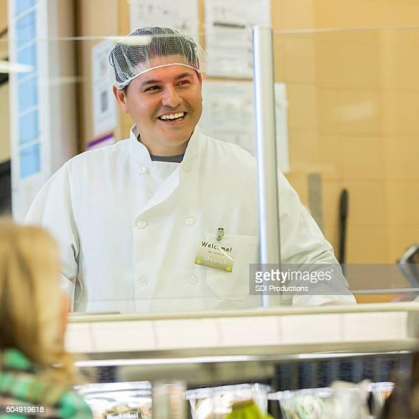 Hispanic Mann arbeitet als Fleischer im Supermarkt deli