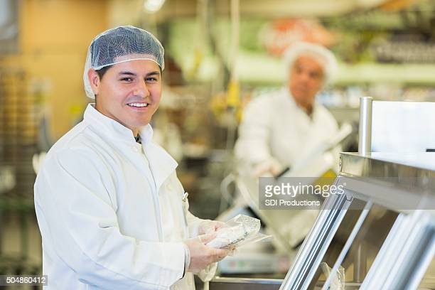 Hispanic man working as butcher or deli manager in supermarket