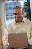 Hispanic man working on a laptop and smiling
