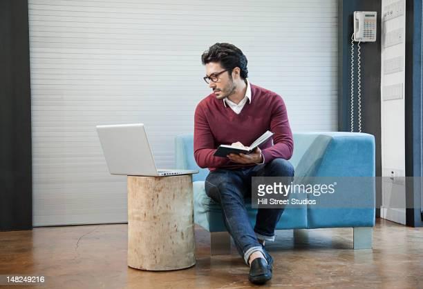 Hispanic man writing and using laptop