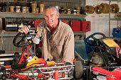 Hispanic mechanic working on go-cart