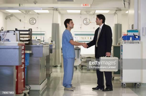 Hispanic medical professional shaking hands with businessman