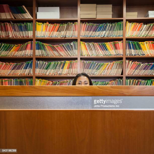 Hispanic medical receptionist behind desk near wall of files