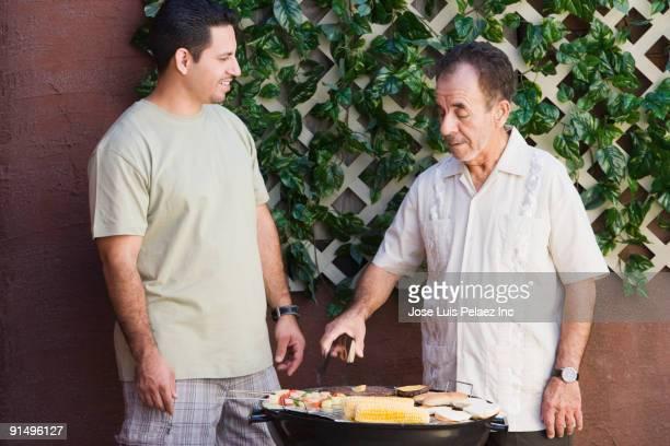 Hispanic men barbecuing on patio