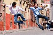 Hispanic men kicking heels in air