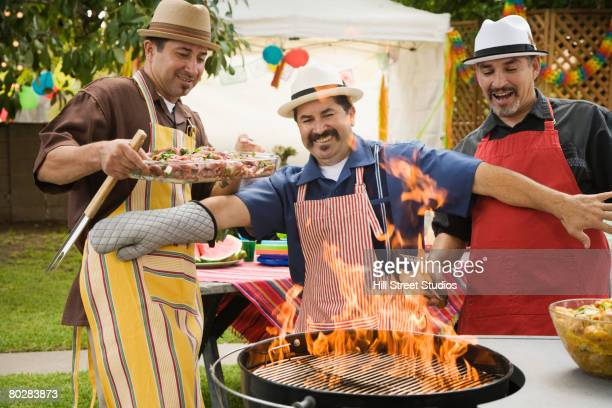Hispanic men leaning back from fire in barbecue grill
