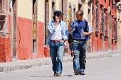 Hispanic men walking in street