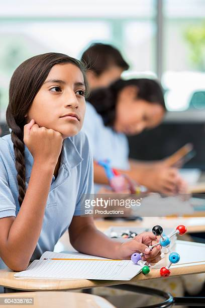 Hispanic middle school student daydreams during science class