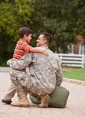 Hispanic military father hugging son