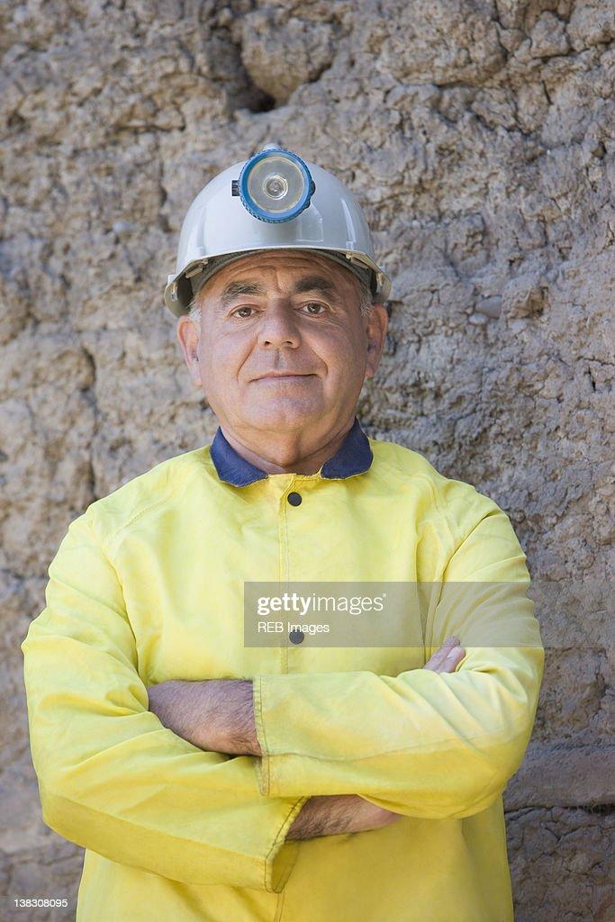 Hispanic miner in coat and hard-hat