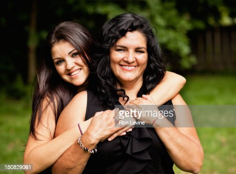 Hispanic mother and adult daughter, hugging : Stock Photo